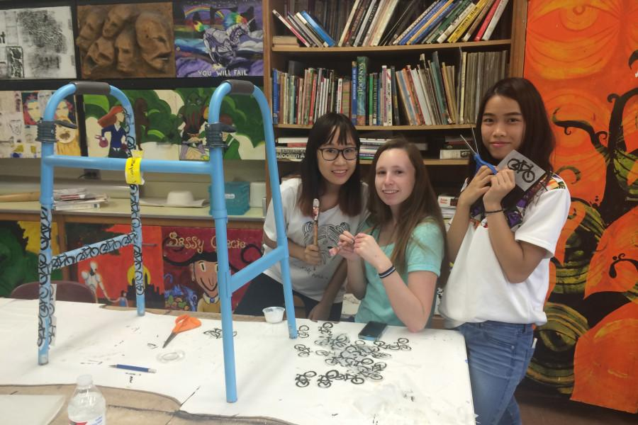 Annika Tran (l), Alexa Long (m) and Phuong Truong (r) help to decorate walkers for the CHS Art Club