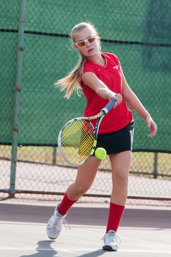 Junior Tori Robinson returns a shot during a girls tennis match this season