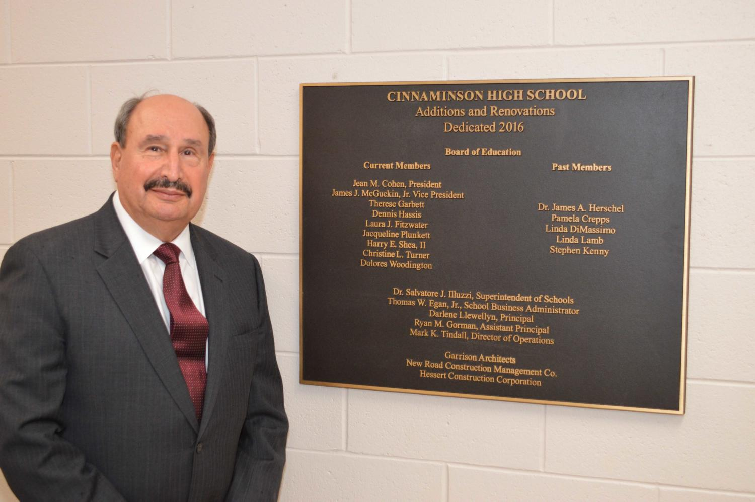 Dr. Illuzzi poses next to the plaque that honors the dedication of the new CHS building.