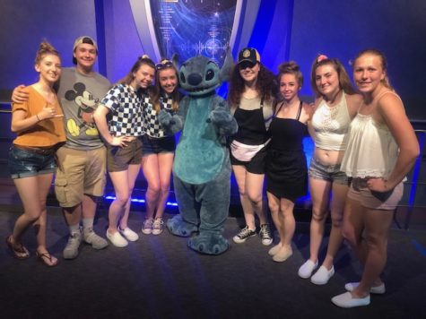 Mikaela and her friends pose for a photo with Stitch from Disney