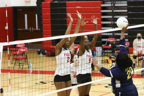 Senior Shelby Sills (left) and Junior Malchiah Blamon (right) set up a block. Photo courtesy of Lors Photography.