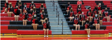 The girls sit socially distanced in the stands for their cheers. Photo courtesy of Coach Kramer and Coach Lamb