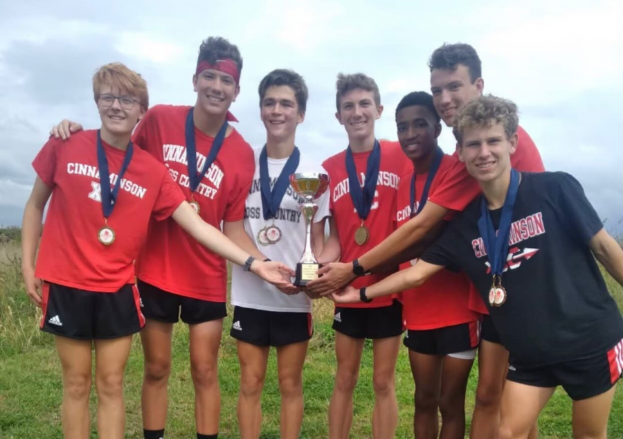 The Boys Cross Country Team poses for a picture with their medals and team trophy on Saturday, Oct. 9, after winning the Division I race at the South Jersey Open at DREAM Park.